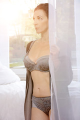 Happy brunette woman in lingerie as underwear stands in sleeping room in front of a window