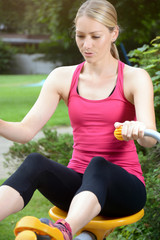 Sporty woman in fitness, training, sport and workout at weight training exercise machine outdoors in the park