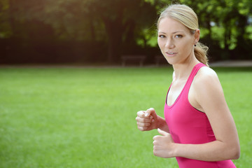 Sporty young blond woman running in the park - Copy Space on meadow