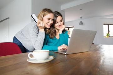 Two joyful girls purchasing in internet store