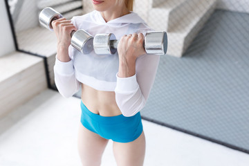 Attractive slender young woman athlete does exercise with dumbbells in the gym. Concept of strength training and fitness