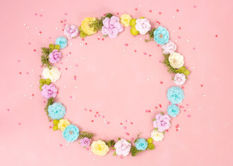 A wreath of multicolored paper flowers and pink and red sweets sugar candy hearts on the Living Coral background . Valentine day. love concept. Spring mood. Space for text. Wide banner - Image.