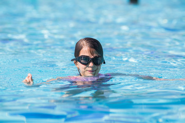 a little girl in a black swimming mask in the pool whith body under the water