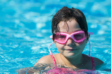 girl in pink glasses in the pool with her head above the water