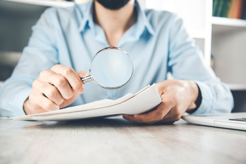 man hand document with magnifier on desk