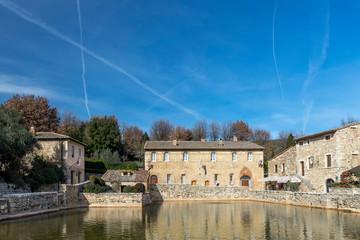 Series of contrails of plane on the sky of Bagno Vignoni, spa village in the province of Siena, Tuscany, Italy