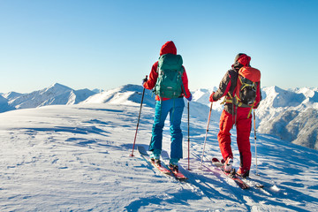 Man and woman ski tourer enjoying the view on a summit in the alps.