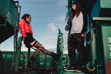 Side view of young hipsters in trendy wear standing on old locomotive on railroad