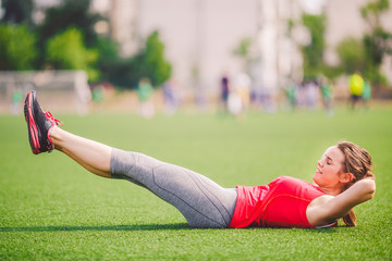 Theme sport and health. Young beautiful Caucasian woman doing warm-up, warming up muscles, abdominal muscles workout, losing belly, abdominal green grass in stadium in the summer on artificial turf