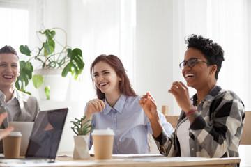 Happy joyful diverse business people laughing talking at work break