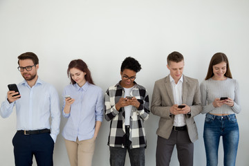 Millennial phone users businesspeople group standing in row using smartphones