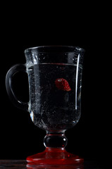 Strawberry in a glass of water with a black background.