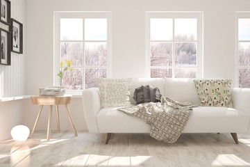 White stylish minimalist room with sofa and winter landscape in window. Scandinavian interior design. 3D illustration