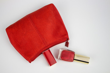 red cosmetic bag with red lipstick and red lacquer. isolate copy space