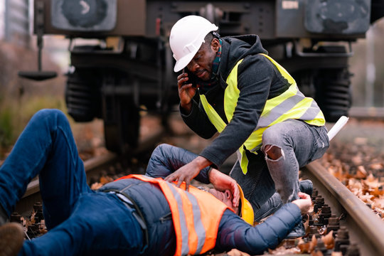 Railroad engineer injured in an accident at work. Railroad engineer injured in an accident at work on the railway tracks. Coworker calling for help