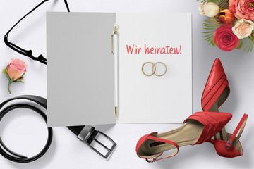 """Grußkarte mit Nachricht """"Wir heiraten!"""", zwei Ringe und Dekoration auf weißem Hintergrund"""