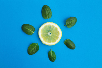 Piece of lemon and mint leaves on the blue background.Creative image of the sun.Top view.Diet minimal concept.