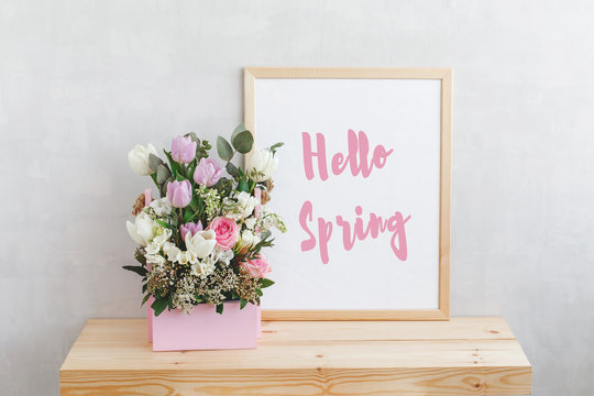 Frame with text HELLO SPRING and spring flower bouquet with tulips, roses, freesia and eucalyptus leaves in pink wooden box on a wooden table on a background of light gray walls. Home interior decor.
