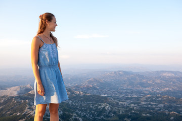 Beautiful girl tourist stands on top of a cliff and admires the beautiful landscape of the mountain range in Montenegro . Tourism, Travel and summer holiday concept