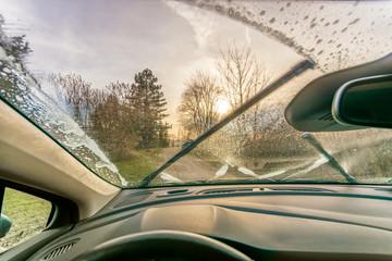Reinigung der Scheibe mit Frostschutzmittel und Scheibenwischern für klare Sicht