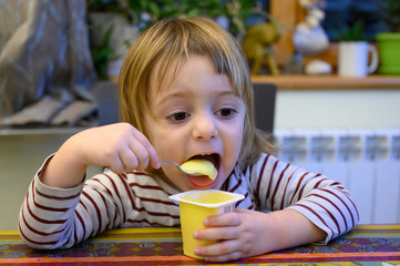 Little girl eating at home