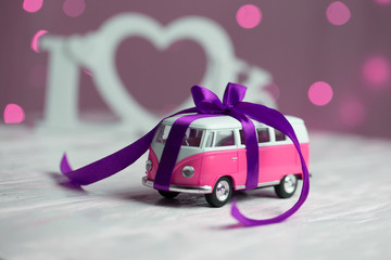 toy car with gift ribbon. toy car with a bow on the background of the word love.