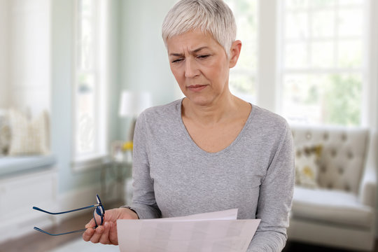 Mature woman with skeptical expression reading contract document or paying bills