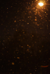 Night dark sky and snow flakes. Night landscape. Falling snow in the light of street lamps at night.