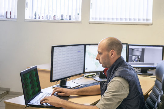 The man  looks at the multitude of monitors in the control room. Specialist of the delivery department works behind the computer. The system administrator checks the server software.