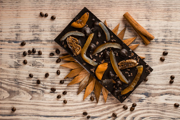 Delicious black chocolate with candied fruits on a wooden stand on a wooden background with a cinnamon stick and grains of coffee.