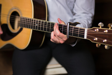 Guitar with a man's male hands playing the guitar on wooden wall background, electric or acoustic guitar with nature light. Concept of guys boys band performing on events