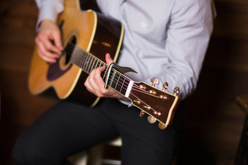 Golden Blues. Man's male hands playing the guitar , singer solo vocal woman on wooden wall background, electric or acoustic guitar with nature light. Concept of jazz boys band performing on events