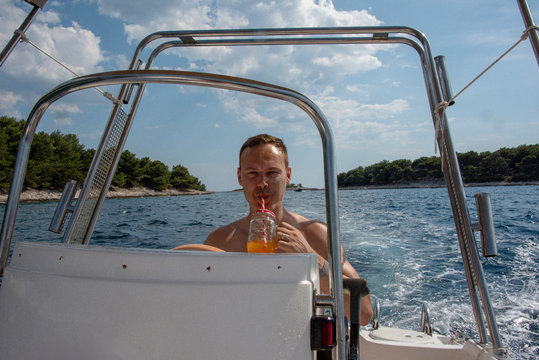 Man drinking while driving a speed boat during vacation