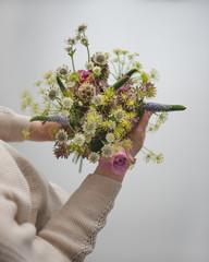 Frau hält bunten Frühlingsstrauss in der Hand