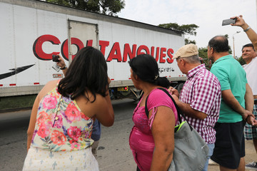 People stand next to the road while trucks arrive at a warehouse, where international humanitarian aid for Venezuela will be stored according to authorities, near the Tienditas cross-border bridge between Colombia and Venezuela, in Cucuta