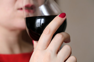 Woman drinking red wine. Seductive girl with manicured nails holds wineglass in hand, concept of degustation, taste enjoying, celebration