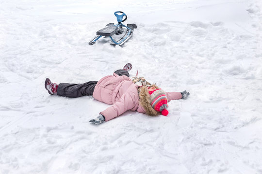 A little girl is lying in snow after falling from his snowmobile, sledge. Children's going sledding.