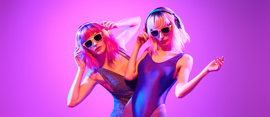Wall Mural - Fashion. Two sexy DJ girl in Colorful neon light dance. Glamour party fitness woman with Dyed Hair in Trendy headphones. Young beautiful model enjoy nightlife. Creative art banner