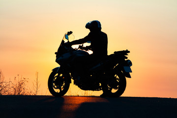 man on his motorbike riding into sunset
