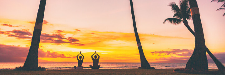Yoga meditation retreat landscape panoramic banner - people meditating on sunset beach praying with hands above head sitting in lotus pose on nature background.