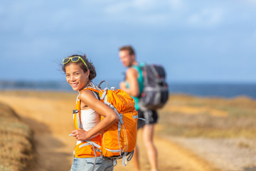 Young happy couple hiking together in nature outdoor. Travel adventure young tourists walking with backpacks in mountain by the ocean.