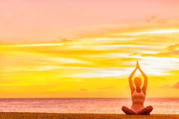 Yoga meditation woman meditating in lotus pose with praying hands in sunset glow on beach.