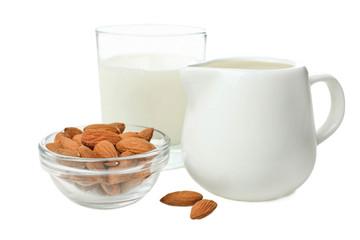 Glass of milk, milk jar and almond nuts