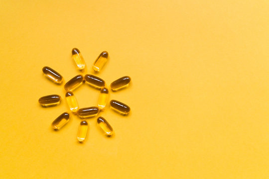 Close up capsules of fish fat oil in the sun shape, omega 3, vitamin e on the yellow background. Healthy food diet. Nutritional supplement