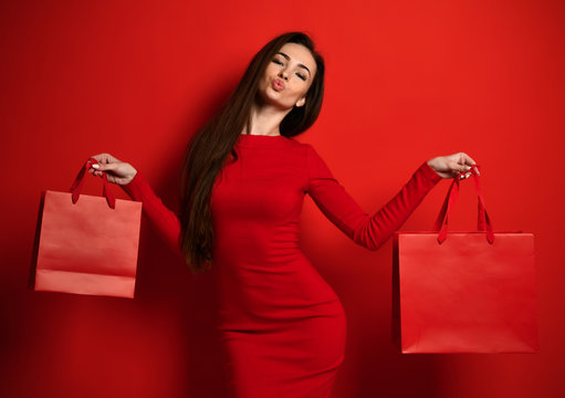 Woman in red tight dress holds two red shopping bags and holds lips like in a kiss