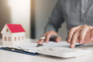 Home agents are using a calculator to calculate the loan period each month for the customer.