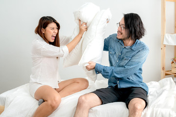 marriage life problem asian couple pillow fight disagree and argue each other on bed bedroom background