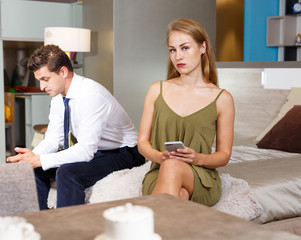 Upset woman with phone and with frustrated man