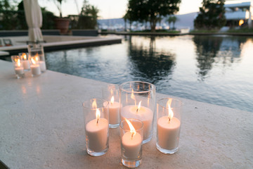 candles are on the side of the pool