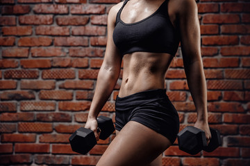 Beautiful athletic woman pumps up muscles with dumbbells against brick wall